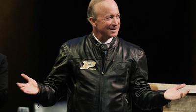 Indiana Gov. Mitch Daniels displays his new Purdue leather jacket given to him by the board of trustee after being named as the next president of Purdue University by the school
