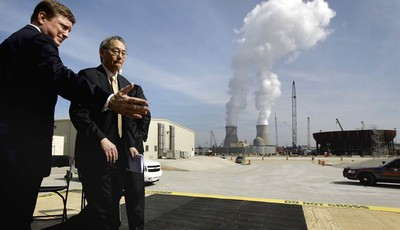 FILE- In this Feb. 15, 2012 file photo, U.S. Secretary of Energy Secretary Steven Chu, right, exits the stage with Southern Company President and CEO Thomas Fanning as cooling towers fo