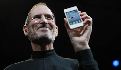 FILE - In this June 7, 2010, file photo, Apple CEO Steve Jobs holds a new iPhone at the Apple Worldwide Developers Conference in San Francisco. Two tech titans are squaring off in feder