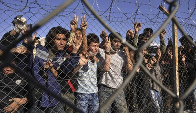 FILE - In this Friday, Nov. 5, 2010 file photo shows young immigrants standing behind a fence at a detention center, in the northeastern Greek village of Filakio near the Greek-Turkish