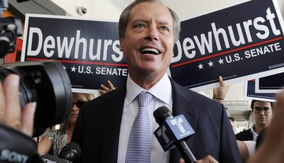 Texas Lt. Gov. David Dewhurst is backed by supporters outside a Houston deli as he answers reporters questions Tuesday, July 31, 2012. Dewhurst faces former Texas Solicitor General Ted