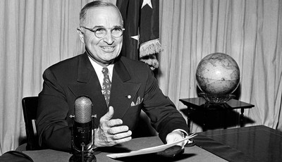 FILE - In this Sept. 1, 1945 file photo, then-U.S. President Harry Truman sits before a microphone at the White House in Washington, where he broadcast a message on the formal surrender