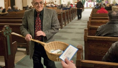 In this Saturday, Dec. 19, 2009 photo, John Alves, of Dartmouth, Mass., uses a basket while taking collection during Mass at St. John the Baptist Roman Catholic Church in New Bedford, M