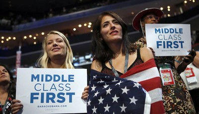 In this Spet. 5, 2012, photo, delegates watch as former President Bill Clinton addresses the Democratic National Convention in Charlotte, N.C. The placards on display as Clinton address