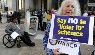 Gloria Gilman holds a sign during the NAACP voter ID rally to demonstrate the opposition of Pennsylvania