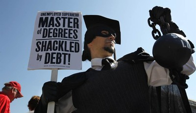 """FILE- In this Oct. 6, 2011, file photo, Gan Golan, of Los Angeles, dressed as the """"Master of Degrees,"""" holds a ball and chain representing his college loan debt, during Occupy DC activi"""