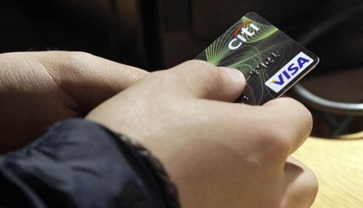 FILE - In this May 9, 2012 file photo, a Visa credit card is tendered at opening of the Superdry store in New York