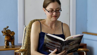This photo taken Oct. 9, 2012 shows Erin Mitchell reading a book on her sun porch outside her home in St. Petersburg, Fla. Which way Florida swings in presidential elections is largely