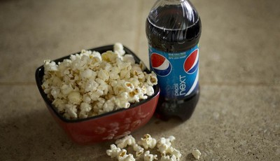 In this Monday, Oct. 15, 2012, photo,  a bottle of  Pepsi is displayed next to popcorn in Pembroke Pines, Fla.  PepsiCo Inc.