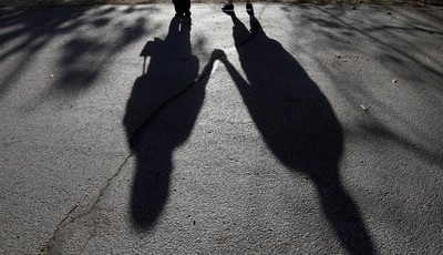 This Sept. 20, 2012 photo shows the shadows of a young woman from Rockford, Ill., left, with her husband. When her doctor said a medical condition made her unplanned pregnancy too risky
