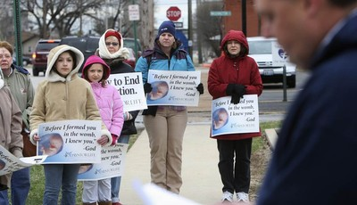 In this March 8, 2011 photo, anti-abortion protesters gather outside the Hope Clinic for Women in Granite City, Ill., as Rev. Chris Comerford, right, from St. Elizabeth