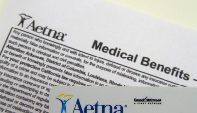 FILE - This Jan. 30, 2012 file photo, an Aetna benefits card is photographed  in Surfside, Fla. Aetna Inc. annoucned Thursday, Oct. 25, 2012, that its third-quarter earnings rose 2 perc