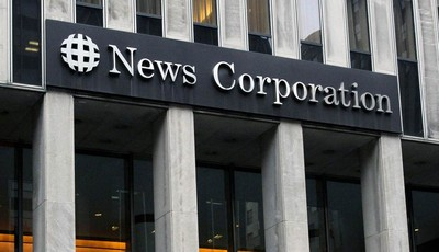 FILE - In this Oct. 12, 2011 file photo, people walk in front of the News Corporation building in New York. News Corp. said Tuesday, Nov. 6, 2012, that net income for the latest quarter