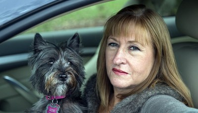 In this photo taken Nov. 2, 2012, Diane Spitaliere and her pet dog Izzie sit in her car outside her house in Alexandria. Baby boomers, that giant population bubble born between 1946 and