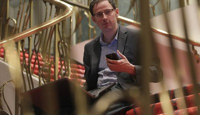 Nate Silver holds his phone as he sits on the stairs with his laptop computer at a hotel in Chicago on Friday, Nov. 9, 2012. The 34-year-old statistician, unabashed numbers geek, author