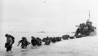 FILE - U.S. reinforcements wade through the surf from a landing craft in the days following D-Day and the Allied invasion of Nazi-occupied France at Normandy in June 1944 during World W