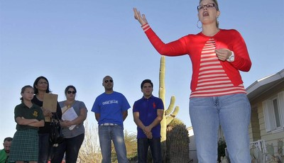 FILE - In a Monday, Nov. 5, 2012 file photo, former Democratic Arizona State Sen. and Arizona congressional candidate Kyrsten Sinema addresses residents in a neighborhood in Mesa, Ariz.