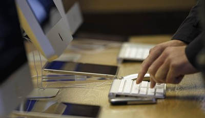 A man uses a computer at a computer shop in central London, Wednesday, Nov. 14, 2012. UK Lawyers say the mounting tally of those arrested and convicted of making offensive comments thro