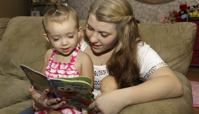 In this Monday, Sept. 10, 2012 photo, Kali Gonzalez reads to her daughter Kiah, 2, at their home in St. Augustine, Fla. A new report by the National Women