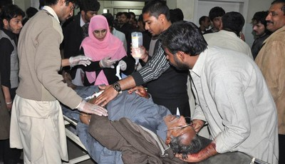 Pakistani hospital staff treat a person injured in a suicide attack on Shiite mourners in Rawalpindi, Pakistan on Wednesday, Nov. 21, 2012. A suicide bomber had tried to enter a process