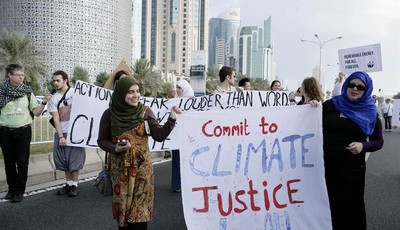 """Qatari Women activists holding a banner reading """"commit to climate justice 4 all """" as they march with local and international activists march to demand urgent action to address climate"""