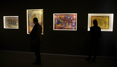 In this photo taken on Thursday, Dec. 5, 2012, visitors look at canvases banned in 1962 by Soviet leader Nikita Khruschev and now exhibited at Moscow