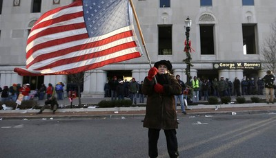 Protester Paula Merwin, of Leslie, Mich., stands with an American flag outside the George W. Romney State Building, where Gov. Snyder has an office in Lansing, Mich., Tuesday, Dec. 11,