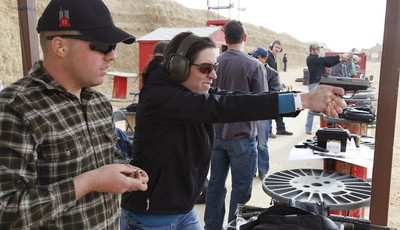 In this Dec. 22, 2012 photo, three weeks back home from the war in Afghanistan, U.S. Army 1st Lt. Aaron Dunn, center, instructs his wife Leanne in effective hand gun operation, at Drago