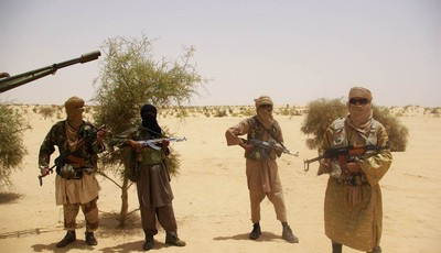 FILE - In this April 24, 2012 file photo, fighters from Islamist group Ansar Dine stand guard during a hostage handover in the desert outside Timbuktu, Mali. In recent months, al-Qaida