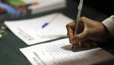 In this Wednesday, Dec. 12 2012 photo a job seeker leaves his contact information with a potential employer during a job fair in New York. Weekly applications for U.S. unemployment bene