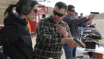 In this Saturday Dec. 22, 2012 photo, U.S. Army 1st Lt. Aaron Dunn, center, instructs his wife Leanne in effective hand gun operation, at Dragonman