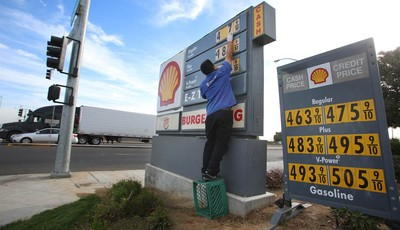 FILE- In this Friday, Oct. 5, 2012, file photo, Luis Cuevas changes the gas prices at the Shell station off California State Route 99. Forecasters say that ample oil supplies and weak U