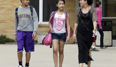 In this April 10, 2013 photo Heather Coffy, right, walks out of St. Monica
