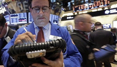 FILE - In this Feb. 8, 2013, file photo, Trader Peter Costa, left, works on the floor of the New York Stock Exchange in New York. The U.S. economy is recovering from the Great Recession