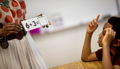 In this Thursday, April 18, 2013 photo, Burgess-Peterson Elementary School second grader Carl Hood, right, sits through a lesson with instructor Lola Onikoyi as part of Atlanta Public S