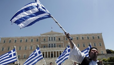 A municipal workers dressed in traditional  costume waves a Greek flag outside Greece