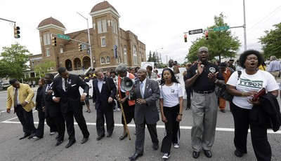 Alabama Southern Christian Leadership Conference Director Bishop Calvin Woods, center with bullhorn, leads thousands of young students on a march through downtown Birmingham, Ala., Thur