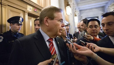 FILE – In this Feb. 14, 2013 file photo Sen. Bob Menendez, D-N.J., speaks to reporters as he enters the Senate chamber at the Capitol in Washington. An ethical cloud is following Menend