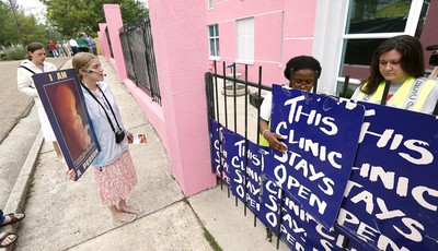 In this April 15, 2013 photograph, abortion opponent Corrie Zastrow, left, calls out to patients while clinic escorts secure signs on the front gates to prevent abortion opponents from