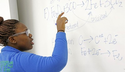 In this Feb. 15, 2013 photograph, Clarksdale High School student Shamia Hopper works on a chemical equation at the dry marker board in her Clarksdale, Miss., classroom. City  leaders ho