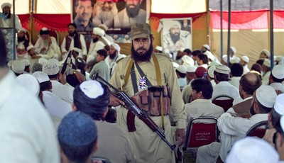 In this Thursday, May 2, 2013, an armed supporter of a pro-Taliban religious group Jamiat-e-Ulema Islam (JUI-F), stands guard as others listen the speech of their leader Maulana Shujaul