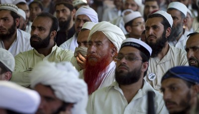 In this Thursday, May 2, 2013 photo, Supporters of a pro-Taliban religious group Jamiat-e-Ulema Islam (JUI-F), listen to their leader Maulana Shujaul Mulk, not pictured, during his an e