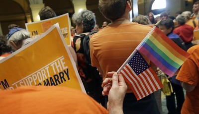 A gay marriage supporter waves the U.S. flag and a rainbow flag as supporters and opponents of Minnesota