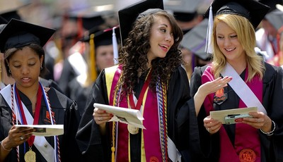 Virginia Tech graduating students, from left: Jasmine Hayes, Kelsey Butler, and Brittany Tatum sing the school Alma Mater at Lane Stadium during the 2013 spring graduation ceremony Frid