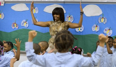 First lady Michelle Obama dances with a pre-K class at Savoy Elementary School in Washington, Friday, May 24, 2013. The Savoy School was one of eight schools selected last year for the
