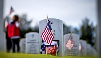 A photo of U.S. Marine Lance Cpl. Corey Allen Little leans against his tombstone as volunteers place American flags at the graves of military service members at Georgia National Cemeter