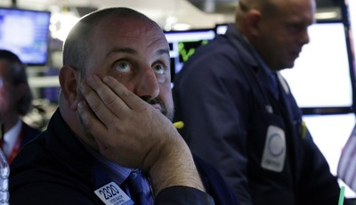 FILE - In this Wednesday, May 29, 2013, file photo, Specialist Peter Giacchi, left, works on the floor of the New York Stock Exchange. Banks and utility companies led stocks higher in m