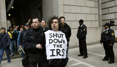 FILE - This March 19, 2008 file photo shows an Iraq War demonstrator gets arrested outside the Internal Revenue Service (IRS) in Washington during a protest on the fifth anniversary of