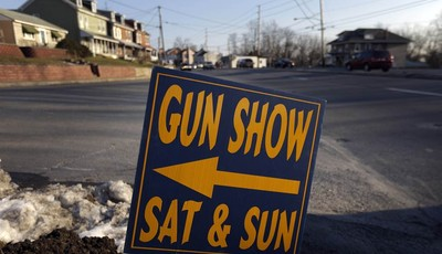 FILE - In a Friday, Jan. 4, 2013 file photo, a sign is posted for an upcoming gun show, in Leesport, Pa. Nearly six in 10 Americans want stricter gun laws in the aftermath of last month