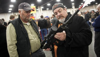 FILE - In a Saturday, Jan. 5, 2013 file photo, gun owners discuss a potential sale of an AR-15, during the 2013 Rocky Mountain Gun Show at the South Towne Expo Center in Sandy, Utah. Ne
